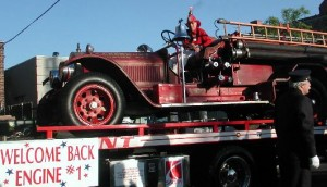 "Ettore Viazzo inspects Engine One, as Walter Bell ""steers"" the pumper as it rides a flatbed to the Memorial Day Parade."