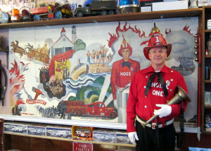 Rich Hargrave in the Historical Fire Company uniform, in front of the Hose Company mural featuring their uniform inspired by the Fire Zoaves.
